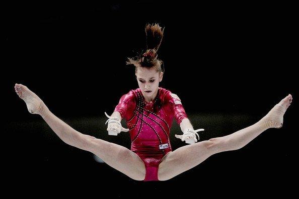 Виктория Комова выполняет программу на разновысоких брусьях