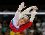 Алия Мустафина выполняет упражнение на разновысоких брусьях